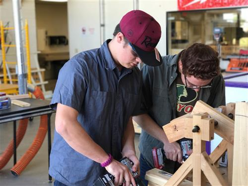 two students working on a project in construction class
